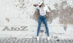 Hipster girl wearing blank white t-shirt, jeans and baseball cap posing against rough street wall, f